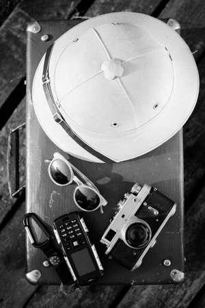 m�dula: Negro blanco Vista photography parte superior m�dula casco, c�mara, gafas de sol y tel�fono m�vil en la parte superior de la maleta retro. exploraci�n concepto