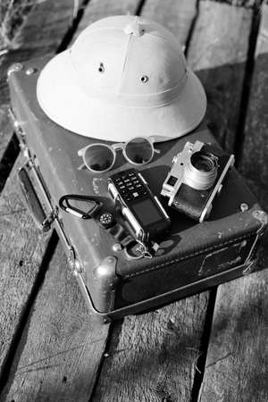 naturalist: Black white photography top view pith helmet, camera, sunglasses and cellphone on top of retro suitcase. Exploration concept