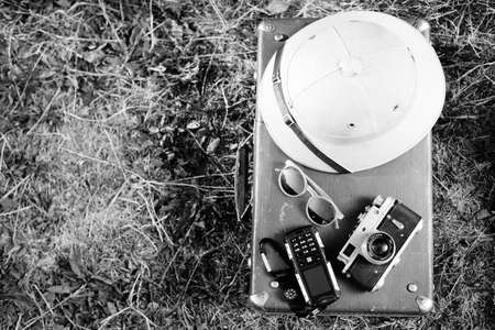 black and white photography: Black white photography top view pithhelmet, old camera, cellphone and sunglasses on retro suitcase, closeup Stock Photo