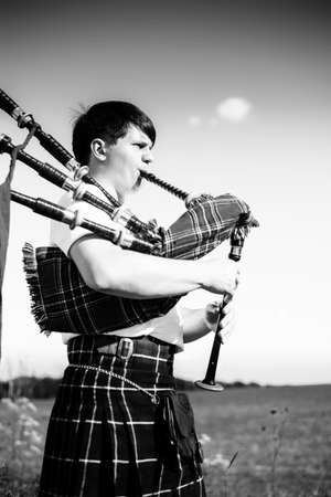 bagpipe: Black and white portrait of young male playing traditional Scotland bagpipe on summer outdoors background