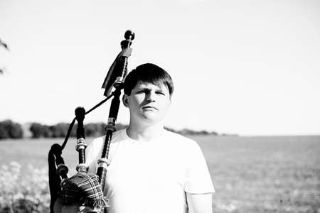 foreign land: Black and white portrait of male holding traditional Scotish bagpipe on summer outdoors copy space background, closeup picture