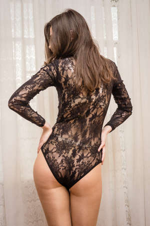Back side view of sensual woman over light window