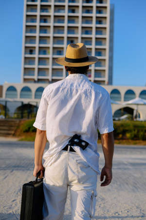 Back view of man with gun holding briefcase in hand on summer blue sky outdoors background