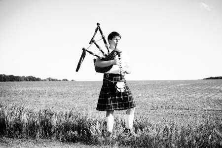 foreign land: Black and white portrait of young male playing traditional Scotland bagpipe on summer outdoors background