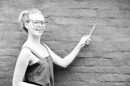 brickwall: Black and white photography of joyful young smiling lady in glasses pointing to the brickwall with pen. Concept of education