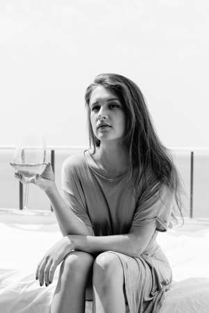 honeymoon suite: Portrait of beautiful woman luxury relaxing in bed enjoying glass of wine on sky sea outdoors background. Black and white image