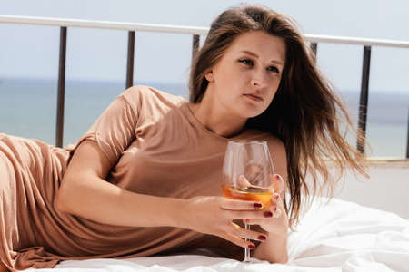 honeymoon suite: Portrait of beautiful woman luxury relaxing in bed enjoying glass of wine on blue sky sea outdoors background