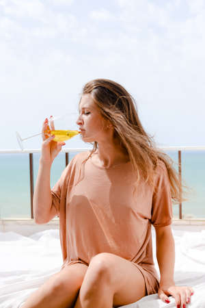 honeymoon suite: Portrait of attractive woman relaxing in bed enjoying glass of wine on blue sky sea outdoors background. Enjoyment and luxury lifestyle