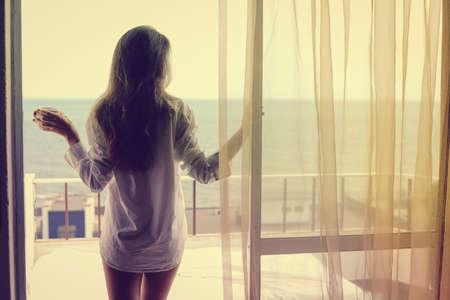 honeymoon suite: Back view of beautiful woman luxury relaxing enjoying cup of coffee tea on blue sky sea outdoors background