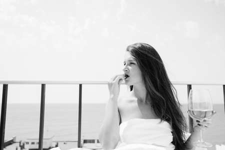 honeymoon suite: Black and white portrait of attractive woman relaxing in bed enjoying glass of wine and strawberries on sunny sky sea outdoors background. Enjoyment and luxury lifestyle.