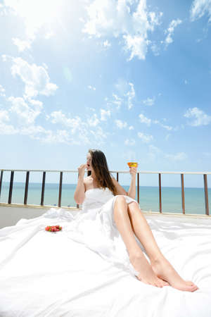 Portrait of attractive woman relaxing in bed enjoying glass of wine and strawberries on blue sky sea outdoors background. Enjoyment and luxury lifestyle