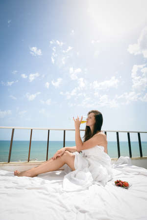 honeymoon suite: Portrait of attractive woman relaxing in bed enjoying glass of wine and strawberries on blue sky sea outdoors background. Enjoyment and luxury lifestyle