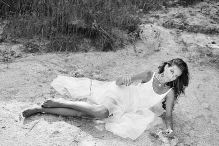 Black and white picture of young woman in dress with fancy necklace and earrings. Pretty girl lying on sand countryside background. Stock Photo