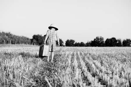 médula: imagen en blanco y negro del niño pequeño que llevaba casco de médula llevar una maleta vieja en el campo. Backview del niño en el mameluco de la tela escocesa que se va en el fondo bengala soleado.