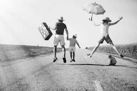Black and white picture of joyful happy family jump on country road in summer. Back view of parents and two kids with suitcase and umbrella on sunny countryside background. Standard-Bild