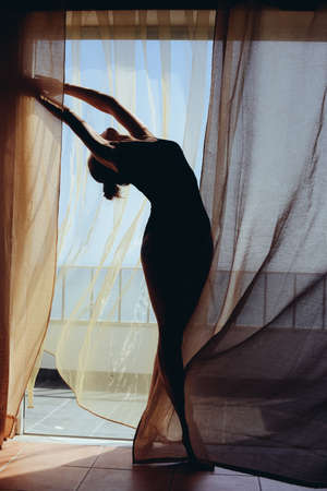 honeymoon suite: Silhouette of beautiful woman enjoying dancing at the window outdoors background Stock Photo