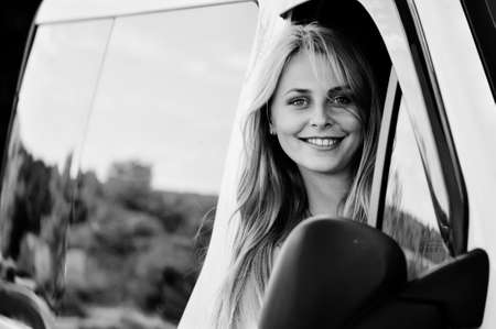 Black and white picture of beautiful woman driving car. joyful female looking from car window at camera on blurred countryside reflection background.