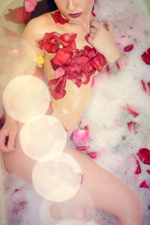 Luxury spa relaxation. Beautiful glamour lady having bath laying in rose petals. Colorful bright background