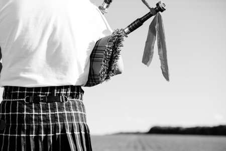bagpipe: Black and white photography of male playing bagpipe on summer outdoors background. Back view closeup