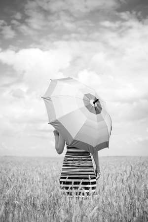 Black and white photography of walking female holding umbrella. Pretty lady in stripped dress in the field outdoors background