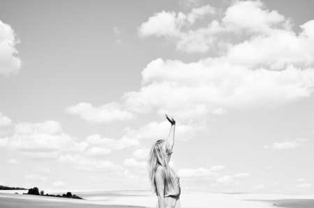 jesus standing: Black and white photography of female lifting arm standing in field over cloudy sky background. Concept of faith