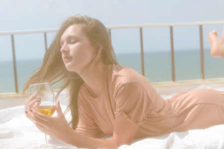 honeymoon suite: Portrait of beautiful woman luxury relaxing in bed enjoying glass of wine on blue sky sea outdoors background