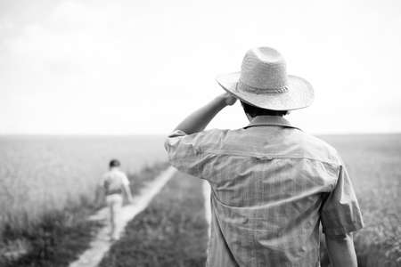 seeker: Black and white picture of man in straw hat looking after boy walking away. Little kid walking alone by countryside road near field on natural outdoors sky background. Stock Photo