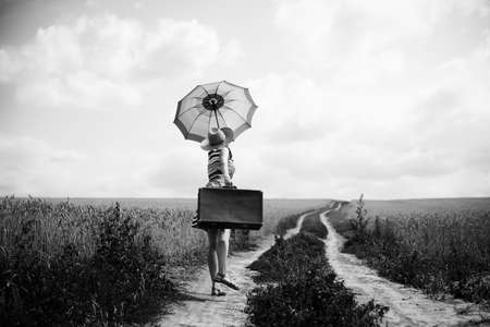 Black and white full length picture of joyful woman dancing on remote country road. Backview of young girl holding retro suitcase on the natural sky sunny outdoors background.