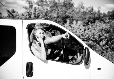 careless: Black and white picture of blond young woman in car speaking on mobile phone and looking from car window. excited girl smiling while talking with someone on summer countryside background. Stock Photo