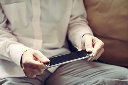 playing on divan: Closeup on mobile phone in hand of man sitting on couch. Top side view mock up background Stock Photo