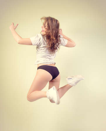 Beautiful young sexy lady with perfectly fit body jumping high on light background in lingerie and sport shoes
