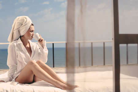 honeymoon suite: Back view of beautiful woman luxury relaxing enjoying cup of coffee tea on blue sky sea outdoors background