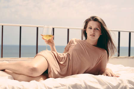 Beautiful woman luxury relaxing in bed enjoying glass of wine on blue sky sea outdoors background Stock Photo