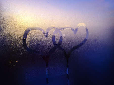 Blurry closeup on love heart sign inscription on condensation indoors glass texture background