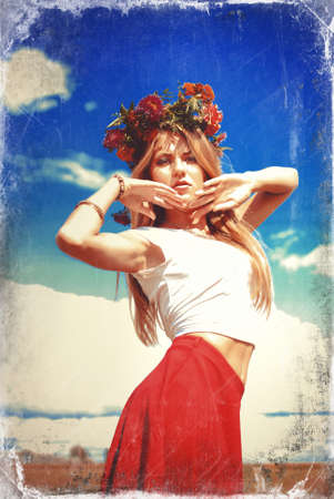 Portrait of amazing girl in wildflower wreath and red skirt in countryside. Young woman with raised hands looking at camera on blurred overexposed outdoor background.