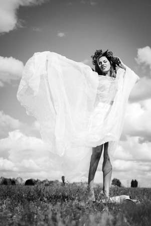 noon: Black and white portrait of attractive girl in flower wreath with white organza shawl dancing on sunny meadow. Young woman barefoot on countryside background.