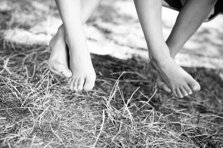 Black and white picture of children legs barefoot. Closeup of happy family sitting on garden swing on sunny countryside background. Stock Photo