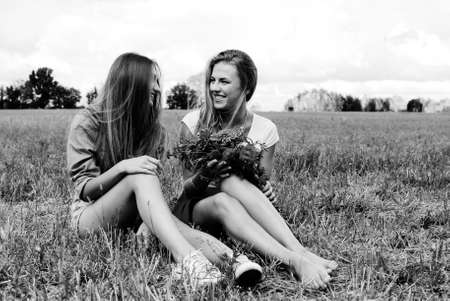 Black and white photography of two charming girls sitting on grass with wildflowers. Young woman talking and happy smiling on summer countryside background. Stock Photo