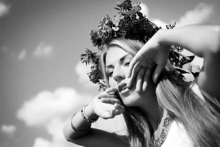 Black and white photography of beautiful girl in marigold wreath and necklace. Young woman with raised hands and open mouth on bright sky background. Close up portrait