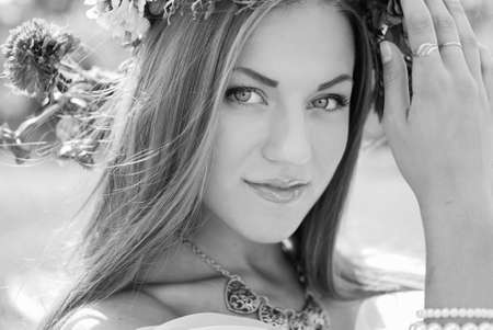 Black and white portrait of beautiful lady in aster and marigold wreath and ethnic necklace. Woman over blurred countryside background.