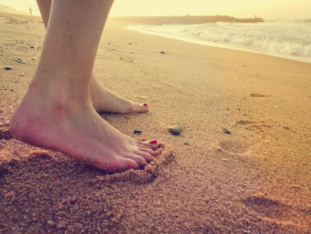 Closeup on woman walking on sandy beach outside background. Natural surface footprints