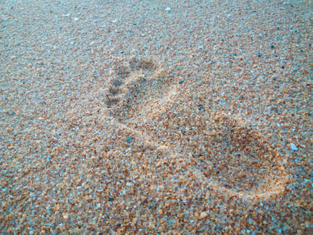Natural background of human footprint in the wet sandy seaside. Close-up photography on relaxation sign idea design