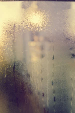 Abstract blurry drops on a transparent rainy window foggy outdoors background texture. Environmental humid climate change