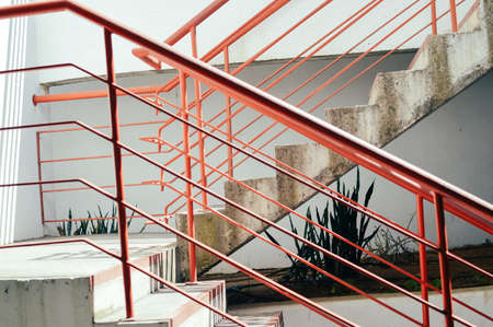 Light staircase with red handrails and concrete walls abstract background