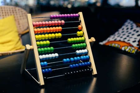 Educational colorful wooden abacus beads on table background. School arithmetic symbol, calculating thinking concept, closeup photography Stock Photo