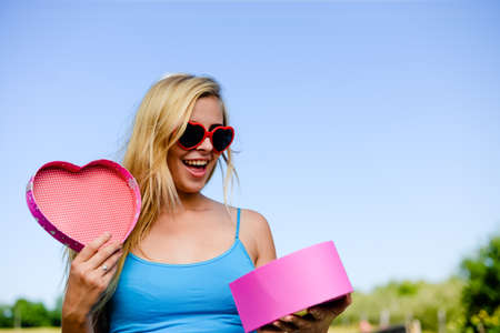 Joyful excited lovely woman holding heart shaped gift box in hands. Happy smiling surprised young lady over light blue sky background. Excitement beauty celebrating moment