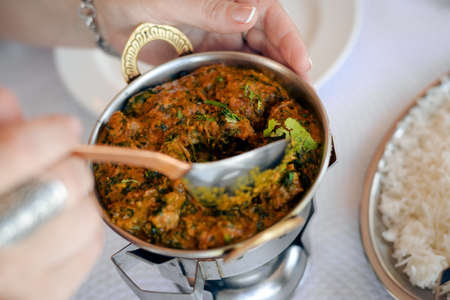 Lamb with spinach, close up of tasty indian food on light table background Stock Photo