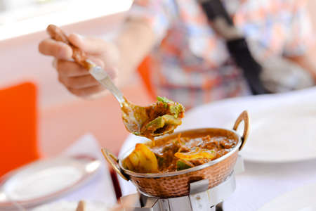 Closeup on Indian speciality curry dish on light restaurant table background. Traditional maincourse delicacy Stockfoto