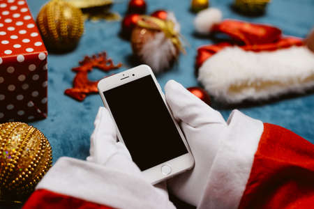 Oslo, Norway - above closeup on Santa Claus holding phone, festive top view shot. Smart communication wireless technology commerce. Shopping ideas browsing organizer Standard-Bild