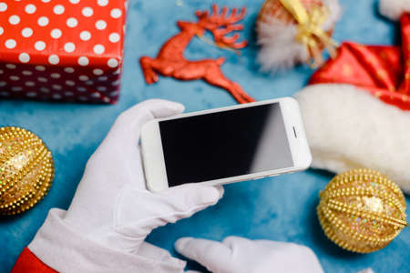 Close up on Santa holding use smart phone, mockup copyspace Christmas eve. Business wireless application for shopping delivery. Portable camera online internet technology. Hat, toy, decor happy event